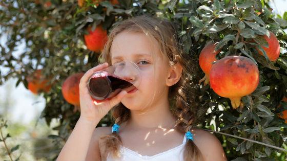 Ребенок пьет гранатовый сок
