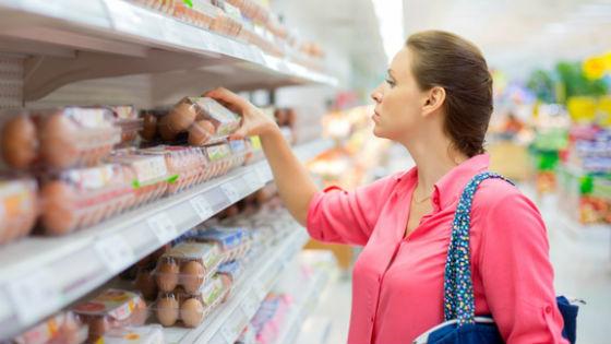 Девушка выбирает яйца в магазине