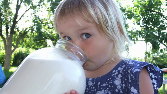 Девочка пьет молоко из банки
