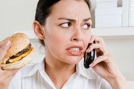 Девушка говорит по телефону и ест