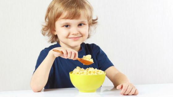 Ребенок ест кашу из пшена
