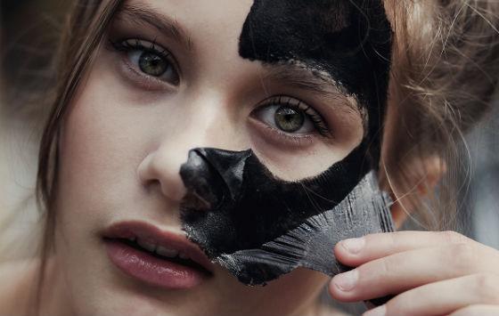 Девушка удаляет маску с активированным углем на основе желатина
