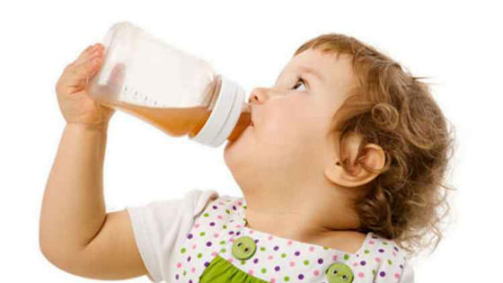 Ребенок пьет сок из бутылочки с соской