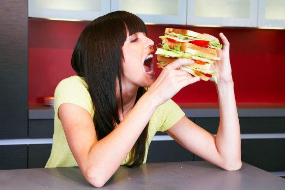Девушка ест большой бутерброд на кухне